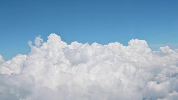 4K Nad mraky z okna letadla s modrou oblohou
