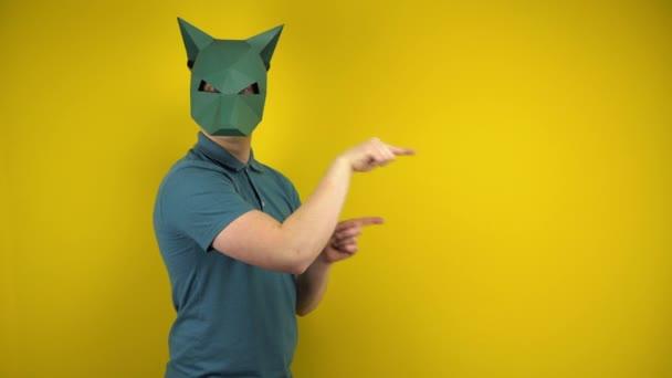 Egy kartondobozos sakál maszkos fiatalember az üres helyre mutat, a mutatóujjaival a sárga háttéren. Férfi zöld pólóban és maszkban..