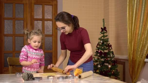 Eine Tochter mit einer jungen Mutter rollt den Teig mit dem Nudelholz in der Küche für Plätzchen zu Weihnachten aus. Das Kind hilft Mama beim Kochen.