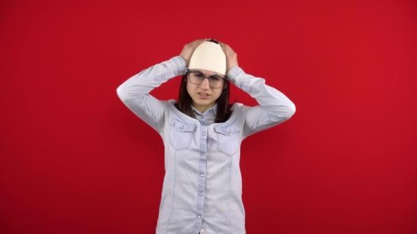 Die junge Frau hat einen Verband am Kopf, den sie vor Schmerzen mit den Händen hält. Schießen auf rotem Hintergrund.