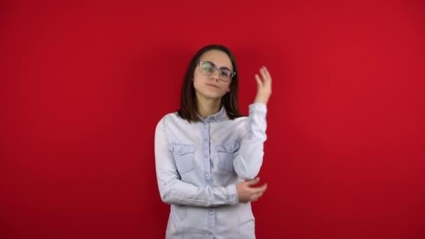 Eine junge Frau mit Brille hat Kopfschmerzen und hält sie in den Händen. Schießen auf rotem Hintergrund.