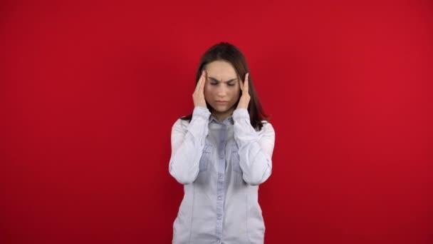 Eine junge Frau mit Brille hat Kopfschmerzen, sie massiert ihre Schläfen. Schießen auf rotem Hintergrund.
