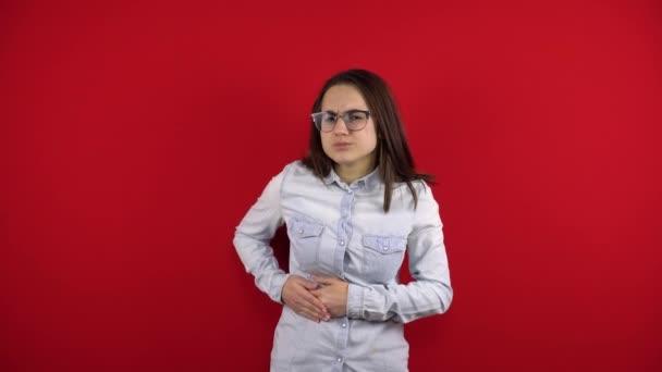 Eine junge Frau mit Brille hat Leberschmerzen, sie hält ihre Seite mit der Hand. Schießen auf rotem Hintergrund.