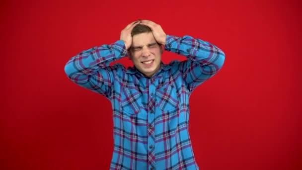 Ein junger Mann hat Kopfschmerzen und hält sie in den Händen. Schießen auf rotem Hintergrund.