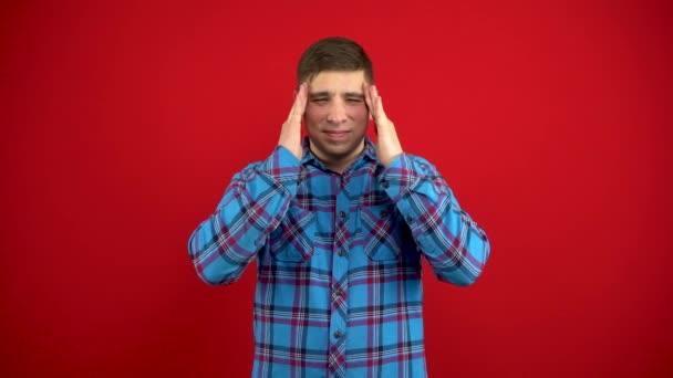 Ein junger Mann hat Kopfschmerzen, sie massiert seine Schläfen. Schießen auf rotem Hintergrund.