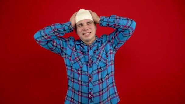 Der junge Mann hat einen Verband am Kopf, er hält ihn wegen der Schmerzen mit den Händen. Schießen auf rotem Hintergrund.