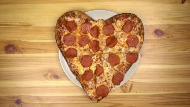 Srdce ve tvaru pizzy na Valentýna. Mladá žena a muž vzít plátky pizzy.