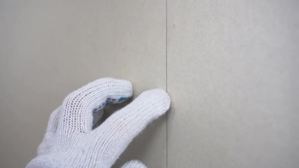 The builder screws the gypsum board with a self-tapping screw using a screwdriver on the wall closeup.