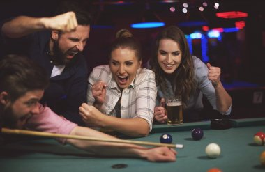 Friends supporting man while playing snooker
