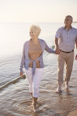 Senior couple walking in the sea water