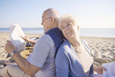 Senior couple reading on the beach
