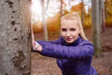 sporty woman stretching in the forest