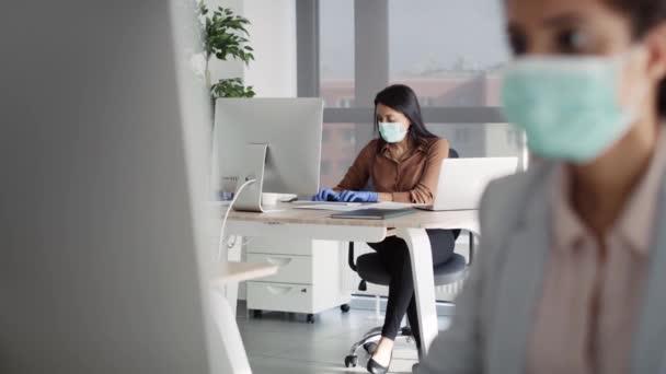 Video von Frauen mit Mundschutz bei der Arbeit im Büro. Aufnahme mit roter Heliumkamera in 8K.