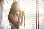 Fotografie Žena v ložnici s kávou