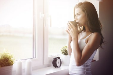 Young woman in bedroom drinking morning coffee. What a great way to wake up! stock vector