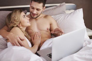Couple enjoing internet in bed