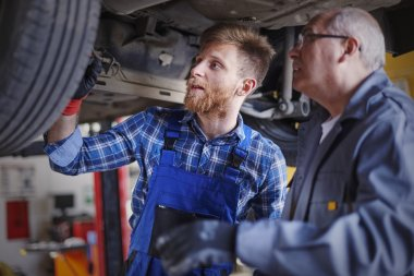 Two mechanics at the service reparing a car stock vector