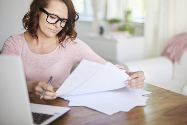 Woman works with documents at home