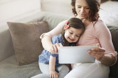 Mother and cute daughter with digital tablet