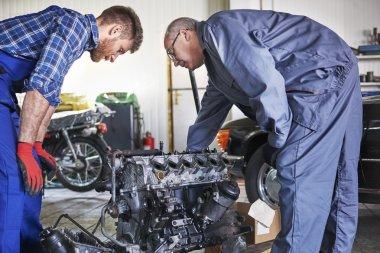 Two mechanics  repairing car's engine