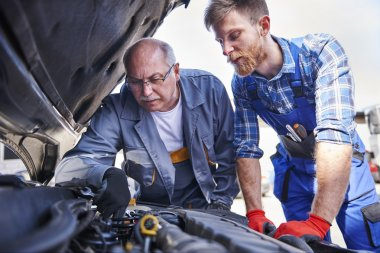 Auto mechanics working in workshop