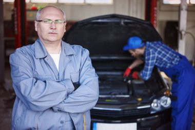 Auto mechanic with arms crossed