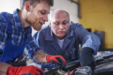 Auto mechanic with worker in action
