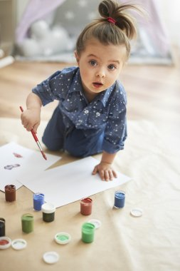 Little girl draws pictures by paintbrush.