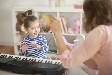 Mother and daughter play on musical instruments