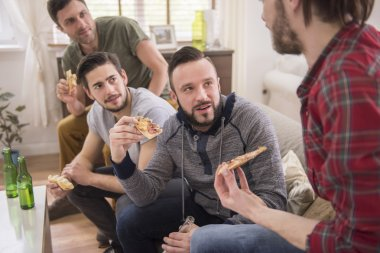 Men eating pizza and drinking a beer