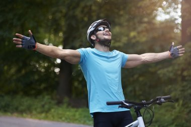 Young man on bicycle feeling happy