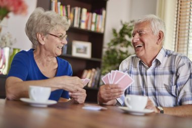 Happy mature couple playing card