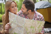 Fotografie Couple looking for their destination on map