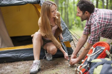 Couple helping each other on camping