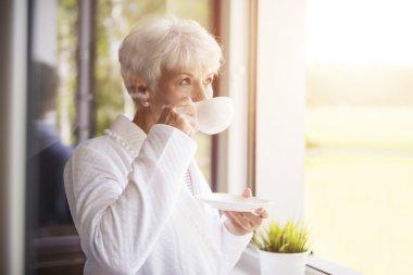 Beautiful mature woman drinking coffee stock vector