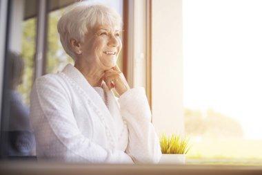 mature woman smiling  near window