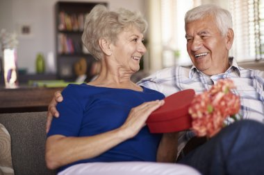 Senior man preparing gift box for his wife