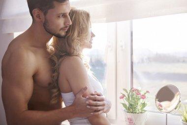 Charming couple next to window