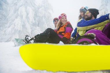 Friends preparing for snowboarding at ski slope