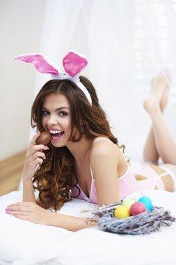 Sweet woman eating chocolate egg