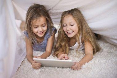 Girls using digital tablet under sheet.