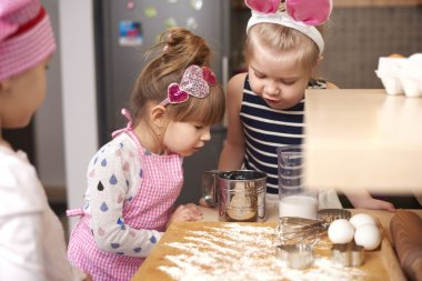 Sisters baking cookies. Very curious how to make a cake stock vector