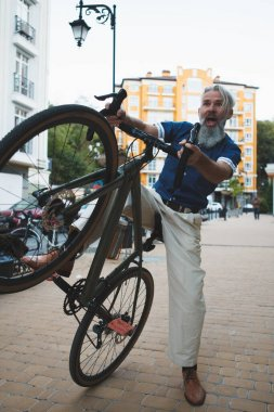 Full length vertical shot of an elderly bearded man with grey hair having fun, posing playfully with his bicycle on city street