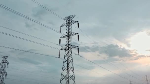 Drohnenaufnahme eines neu errichteten elektrischen Sendeturms auf einem grünen Reisfeld bei Sonnenuntergang