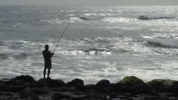Kuta, Kabupaten Badung, Bali, Indonézia - 2020. november 6.: Indonéz halász nagy hullámokkal és sziklákkal
