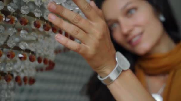 Mladá krásná evropská dívka dlouhosrstá brunetka modelka vzhled stojí v blízkosti lustru a dotýká se jí rukama