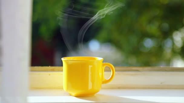 Žlutý šálek kávy na parapet