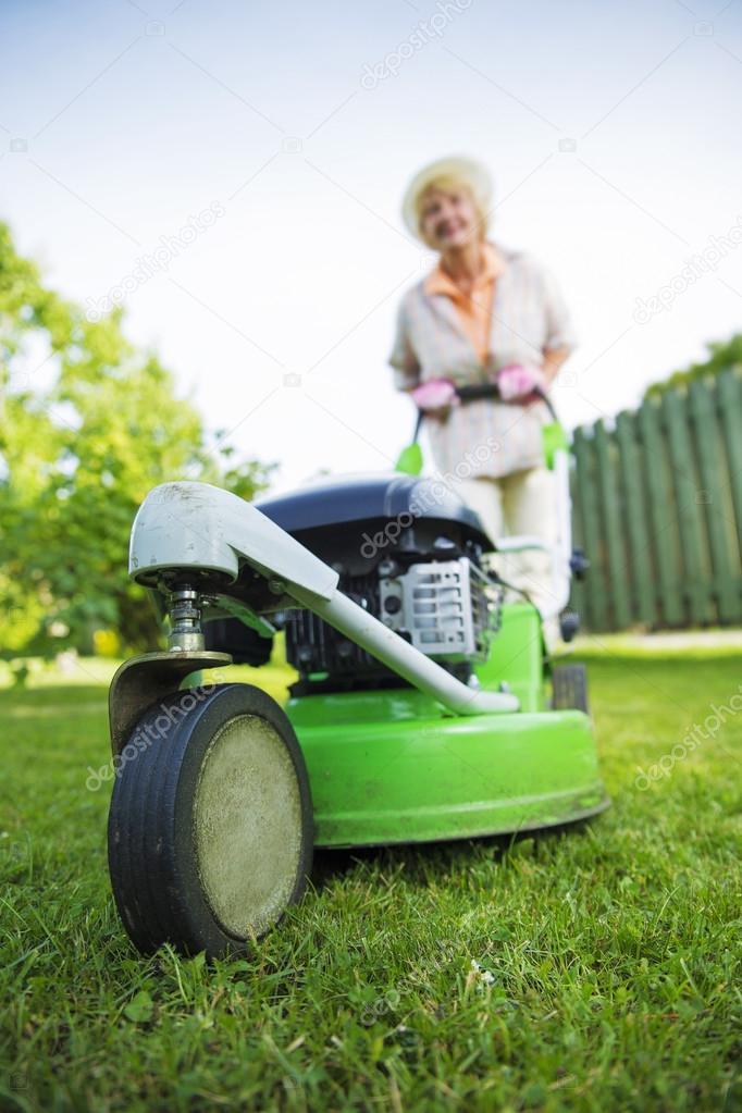 femme tondre la pelouse au jardin yard photographie. Black Bedroom Furniture Sets. Home Design Ideas