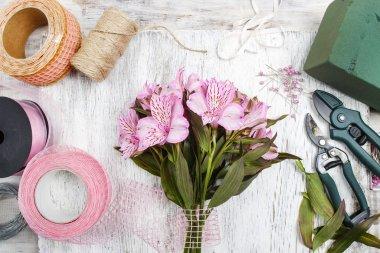 Florist at work: woman arranging bouquet of alstroemeria flowers
