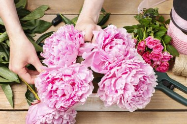 Florist at work: woman making floral decoration of pink peonies